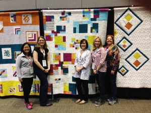 Some of the members of the Southern CT Modern Quilt Guild in front of our guild's charity quilt.