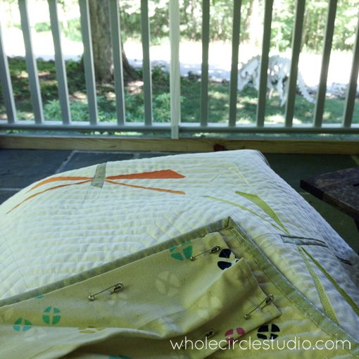 Day 112: 365 Days of Handwork Challenge — Stitching a sleeve on this Dragonfly Dance Quilt so it can go off to Urban Sew Fabric Shop for their booth at in Grand Rapids American Quilt Week. The weather is beautiful on my front porch today and our plynosaur (plywood dinosaur) is keeping me company. Whole Circle Studio — 365 Days of Handwork Challenges
