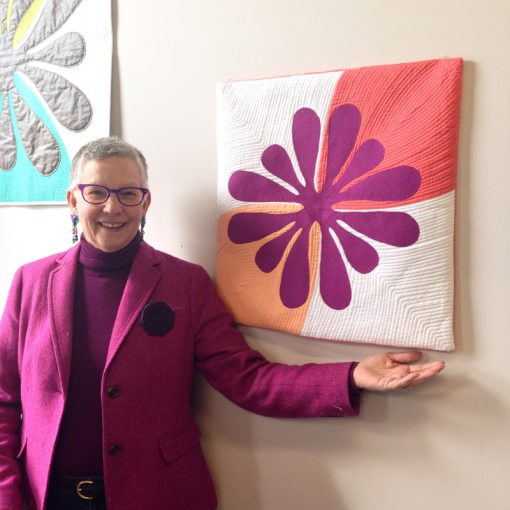 Pat Ryan, shopkeeper of Ryco, Inc. with Big Island Blossom by Sheri Cifaldi-Morrill | Whole Circle Studio. A modern, Hawaiian-inspired quilt.