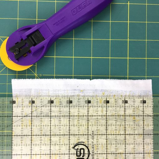 Squaring up and trimming fabric for a quilt.