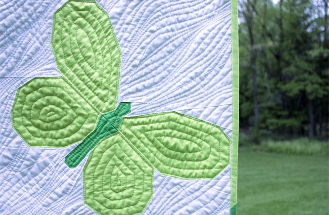 detail of Butterfly Bunch throw size quilt. Designed and made by Sheri Cifaldi-Morrill of Whole Circle Studio with cotton quilting solids. These butterfly patchwork blocks are foundation paper pieced and can be made into the perfect wall hanging, throw, twin, queen or king quilt to give as a gift.