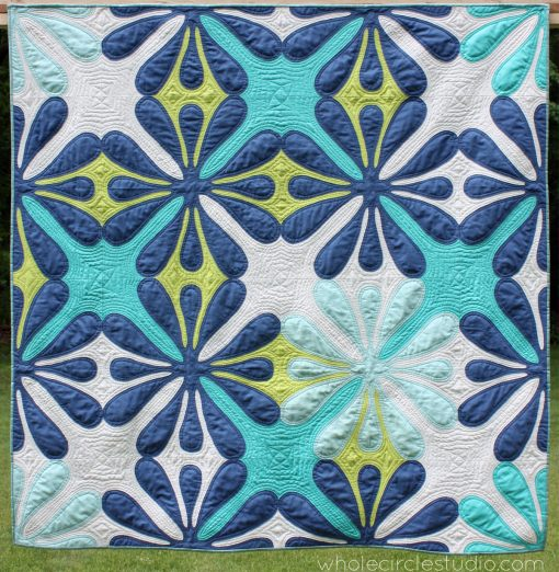 Big Island Blossom: a hawaiian inspired needle turn applique quilt. Pattern by Whole Circle Studio. A modern spin on traditional Hawaiian Quilts. Inspired by her love of the Big Island, Sheri designed and needle turn appliqued most of this quick while on a vacation in Hawaii.