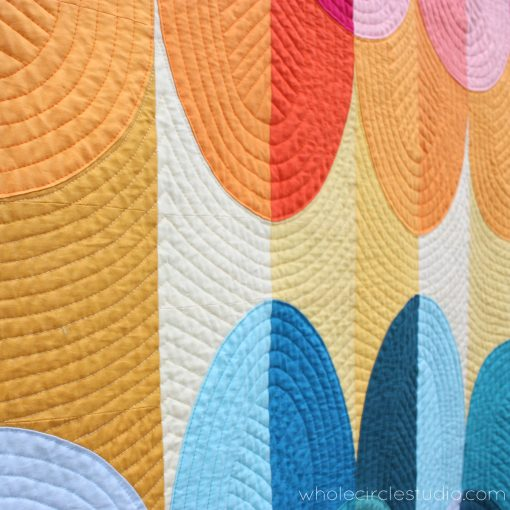 detail of Kona Sunset, a modern curve Drunkard's Path quilt using solid fabrics. Inspired by Hawaiian sunsets on the Big Island in Kona. Design by Sheri Cifaldi-Morrill of Whole Circle Studio.