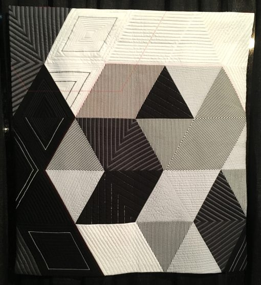 """""""Number 16"""" by Miquel Huidor. Statement: """"With this quilt I wanted to take a traditional shape, the triangle and really modernize it. The quilt is layered in images with the triangles, the hexagons, the stripes, and the small hints of color. I also explored moving away from printed quilt fabrics to more yarn-dyed fashion fabrics. The result is a more elevated finish to the quilt. [Design Source: Original Design] """"Number 16"""" by Miquel Huidor. Statement: """"With this quilt I wanted to take a traditional shape, the triangle and really modernize it. The quilt is layered in images with the triangles, the hexagons, the stripes, and the small hints of color. I also explored moving away from printed quilt fabrics to more yarn-dyed fashion fabrics. The result is a more elevated finish to the quilt. [Design Source: Original Design] displayed in the 2018 Modern Quilt Showcase sponsored by the Modern Quilt Guild at the International Quilt Festival in Houston"""