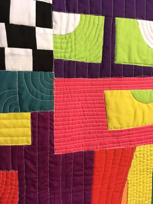 "detail of ""Crazy Town Roopetoope"" by Irene Roderick displayed in the 2018 Modern Quilt Showcase sponsored by the Modern Quilt Guild at the International Quilt Festival in Houston"