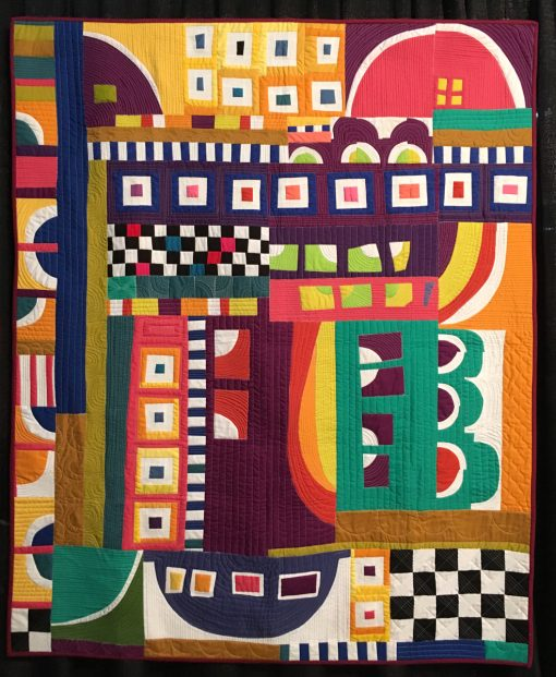 """Crazy Town Roopetoope"" by Irene Roderick Statement: ""This quilt is one of the first quilts in what I consider my true voice. After trying to figure out what modern quilting was supposed to be, I threw caution of the wind and just started making elements, putting pieces of fabric on thew all then rearranging them until I found the perfect arrangement. I didn't pay attention to how to construct the pieces into a quilt, but only enjoyed playing!"" [Design Source: Original Design] displayed in the 2018 Modern Quilt Showcase sponsored by the Modern Quilt Guild at the International Quilt Festival in Houston"