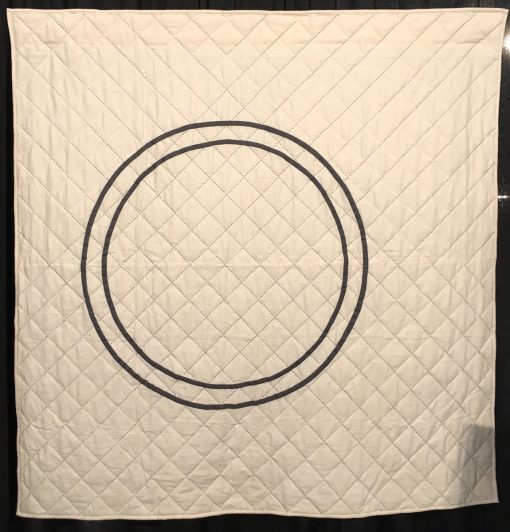 """Counterpart"" by Riane Menardi Morrison Statement: ""This quilt is my modern take on a Wedding Ring quilt. After getting married in fall 2017, I started designing and making quilts that represent my idea of home and family. This quilt design was inspired by two wedding rings—mine and my husband's. The 1/2 rings are appliqued on a wholecloth background. The quilt is hand-quilted using large sashiko thread in two colors. The quilting motif emanates from the center of the rings, representing two lives coming together."" [Design Source: Original Design] displayed in the 2018 Modern Quilt Showcase sponsored by the Modern Quilt Guild at the International Quilt Festival in Houston"