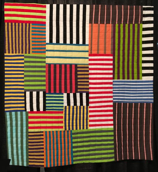 """Striped Chaos"" by Maria Shell Statement: ""When making the quilts from my book Improv Patchwork—Dynamic Quilts Made with Line and Shape, I wanted to show the design potential present in the simple stripe, also known in the quilting world as a strip set. This quilt is an off-the-grid composition based solely on machine pieced striped fabric."" [Design Source: Traditional strip sets] displayed in the 2018 Modern Quilt Showcase sponsored by the Modern Quilt Guild at the International Quilt Festival in Houston"