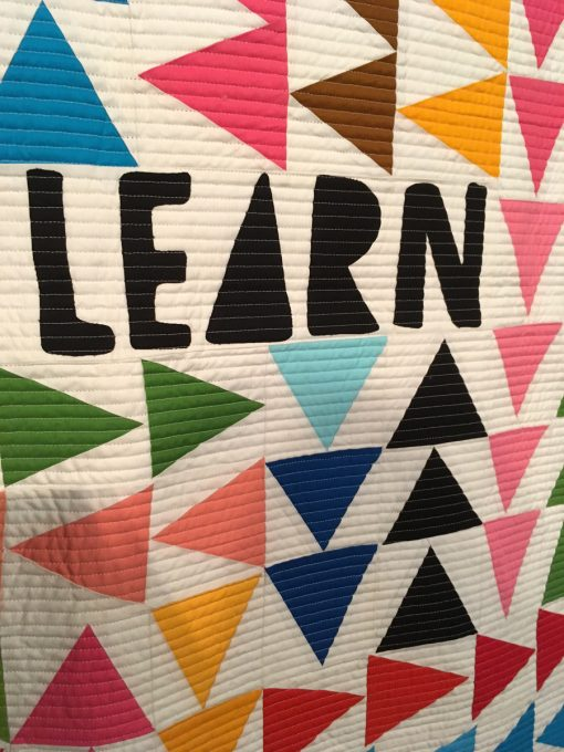 """detail of """"Show Up"""" by Sam Hunter. Quilted by Nancy Stovall. Constructed by Maria Cardenas, Nicole Howe, Linda Nussbaum, Amy Qualls, Matthew Stovall, Nancy Stovall, and Megan Woolery displayed in the 2018 Modern Quilt Showcase sponsored by the Modern Quilt Guild at the International Quilt Festival in Houston"""