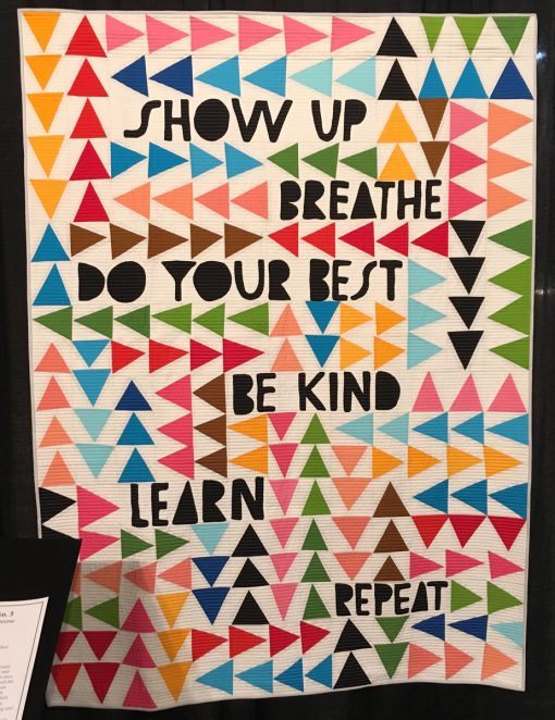 """""""Show Up"""" by Sam Hunter. Quilted by Nancy Stovall. Constructed by Maria Cardenas, Nicole Howe, Linda Nussbaum, Amy Qualls, Matthew Stovall, Nancy Stovall, and Megan Woolery. Statement: """"When Lisa published this design, Show Up, as a poster, I approached her to adapt the design into a quilt pattern. I am a self-professed 'word girl' and so was excited to help produce a pattern with such a timeless message. The construction was assisted by my sewing pals, the Stunt Sewists."""" [Design Source: Design adapted by Sam Hunter from artwork by Lisa Congdon] displayed in the 2018 Modern Quilt Showcase sponsored by the Modern Quilt Guild at the International Quilt Festival in Houston"""