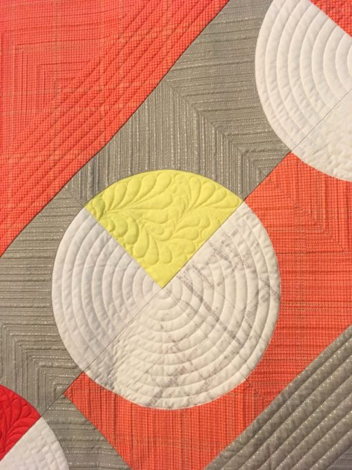 "detail of ""Give and Take"" by Kari Vojtechovsky. Quilted by Christine Perrigo displayed in the 2018 Modern Quilt Showcase sponsored by the Modern Quilt Guild at the International Quilt Festival in Houston"