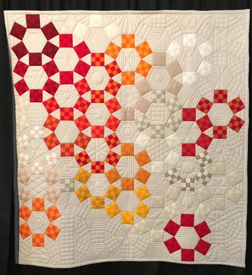 """Unchained Melody"" by Jackie Benedetti. Quilted by Dionne Matthies-Buban. Statement: ""I've always been intriqued by the 1930s pattern Jack's Chain and love how different the pattern looks depending on color placement. I was inspired to make a modern rendition using solids, lots of negative space, and my favorite colors. Dionne's quilting helped highlight the background blocks. Minimal quilting of the Nine Patch blocks helped make them pop. The entire top was hand-pieced except for the Nine Patch blocks."" [Design Source: Jack's Chain pattern] displayed in the 2018 Modern Quilt Showcase sponsored by the Modern Quilt Guild at the International Quilt Festival in Houston"