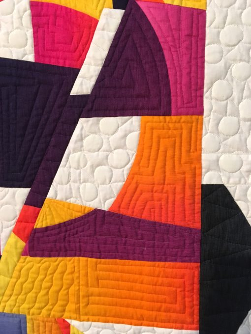 "detail of ""Mid-Century Modern Curve #1"" by Carole Lyles Shaw. Quilted by Carol Byrnes. displayed in the 2018 Modern Quilt Showcase sponsored by the Modern Quilt Guild at the International Quilt Festival in Houston"