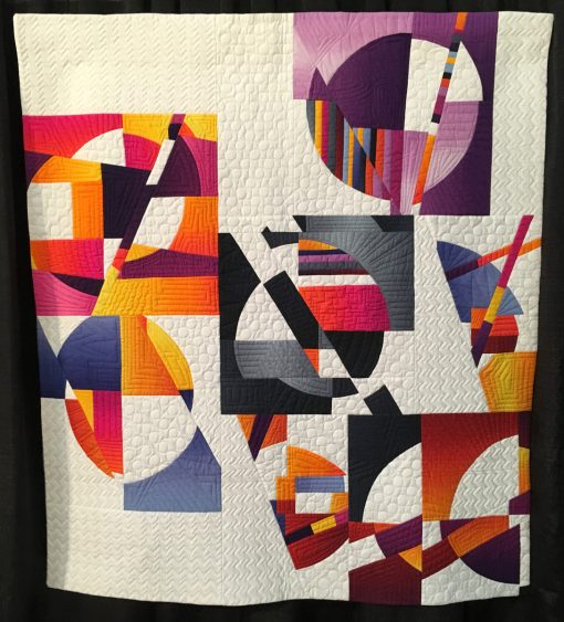 """Mid-Century Modern Curve #1"" by Carole Lyles Shaw. Quilted by Carol Byrnes Statement: ""This is a functional quilt inspired by 20th century art. Specifically, the bold palette was inspired by Color Field painters and the curved motifs found in the works of Sonia Delaunay. The blocks are based on traditional Drunkard's Patch blocks that were improvisationally cut and fractured. I created negative space in and around the blocks and placed it in alternative and asymmetrical layout."" [Design Source: Drunkard's Path block] displayed in the 2018 Modern Quilt Showcase sponsored by the Modern Quilt Guild at the International Quilt Festival in Houston"