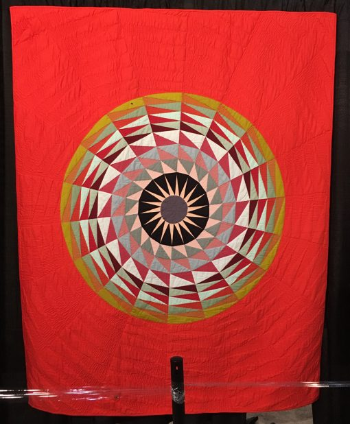 """""""Radiant"""" by Maritza Soto Statement: """"I wanted to make a compass quilt using a fresh modern palette. Inspired by the paintings of Kristin Farr, who in turn was inspired by barn quilts, I employed an analog approach to making this. I used a 10 degree wedge ruler and kraft paper to create paper piecing templates for the radiating wedges. I enjoyed how the result played tricks on the eye."""" [Design Source: Original Design] displayed in the 2018 Modern Quilt Showcase sponsored by the Modern Quilt Guild at the International Quilt Festival in Houston"""