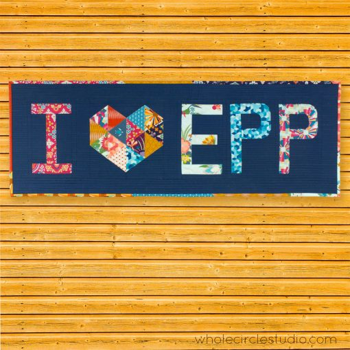"""I Heart EPP mini quilt made with Typecast, an English Paper Piecing (EPP) Pattern Make all 26 letters of the alphabet. Each block measures approximately 6"""" x 9"""". This fully tested pattern guide contains detailed instructions, tips and diagrams to walk quilters through the variety of EPP straight line and curved piecing skills they will use while making Typecast blocks. Required English Paper Pieces and optional acrylic templates not included. Pattern by Whole Circle Studio"""