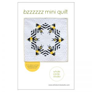 Bzzzzzz is an award-winning modern, graphic wallhanging/mini quilt featuring a combination of traditional machine piecing and foundation paper piecing. Make additional blocks to make a larger quilt (layout ideas are provided to make a lap, twin or queen quilt). This tested pattern contains both detailed instructions and diagrams, making it easy to piece. Pattern by Whole Circle Studio.