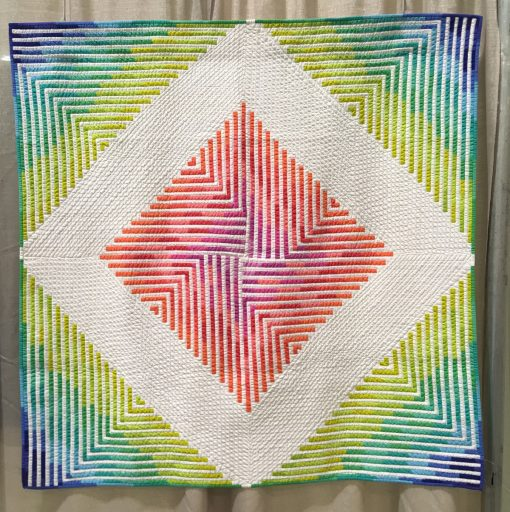 "Modern quilt featured at QuiltCon 2019 — ""Star Sprinkles"" by Steph Skardal www.instagram.com/stephskardal Statement: ""This original design was created in Photoshop. It is the first in a series of quilts taking inspiration from the blending of watercolor paint in a bright, modern color palette mixed with the hardness of geometric (linear) shapes. The modified courthouse steps form a larger diamond shape via negative space. It was machine quilted on a domestic machine using a walking foot."