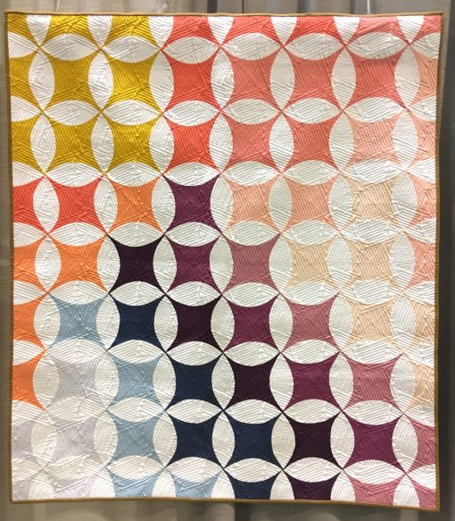 "Modern quilt featured at QuiltCon 2019 — ""Shades of Citrus"" by Brittany Lloyd. Quilted by Jess Ziegler @loandbeholdstitchery Statement: ""Shades of Citrus is a fun spin on the negative space of a classic Lafayette orange peel quilt block."""