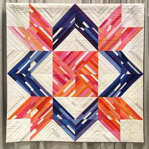 "Modern quilt featured at QuiltCon 2019 — ""Barn Quilt"" by Renee Tallman @uniquilter Statement: ""I like barn quilts and I wanted to make a quilt that had the appearance of being painted. When the SBAMQG issued our Make it Modern challenge in 2017, one option was to modernize the traditional weathervane block. I pieced scraps onto muslin foundations in an improv style. I used many shades as I could to convey the idea of a painted quilt block. I added areas where it looked like the paint was peeling of in layers, appearing worn and rough, as if the barn wood might be aging or showing through the paint. Source: traditional block design, called the weathervane block."