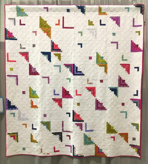 "Modern quilt featured at QuiltCon 2019 — ""Peeling Away"" by Betsy Ryan @rryan3. Quilted by Janice Roy Statement: ""This quilt is an adaptation of the traditional Log Cabin quilt block, the quintessential American design. It represent log cabins on the prairie with the center squares for the hearth, light values on one side for the sunny side of the house, and dark values on the opposite side for the shady side of the house. I wanted this quilt to have a lot of negative space, to be less cluttered, to be freeing. I started out with more complete log cabin shapes and then removed more color and left more negative space."