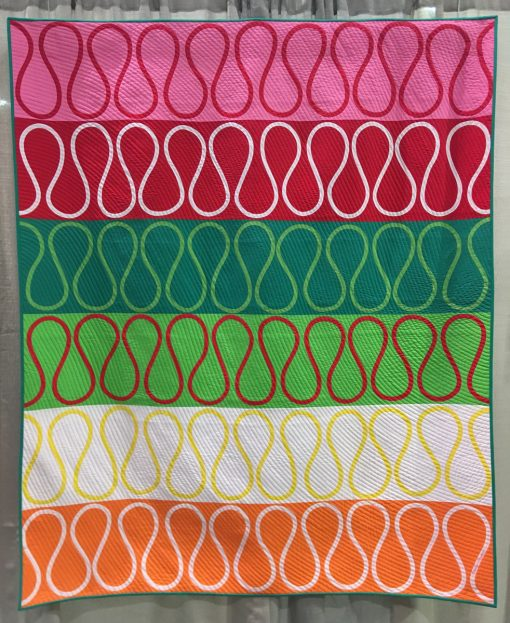 "Modern quilt featured at QuiltCon 2019 —""Ribbon Candy"" by Emily Parson @emilyquilts Statement: ""My family loves ribbon candy! It was a special treat that my grandma had every year at Christmas. Now I buy it for my own kids and they love it as much as I did. I used bias tape applique to recreate the unique shape and festive colors of ribbon candy. Bias tape is easy to manipulate into curves and it comes in lots of great colors. It is a fun process!"""