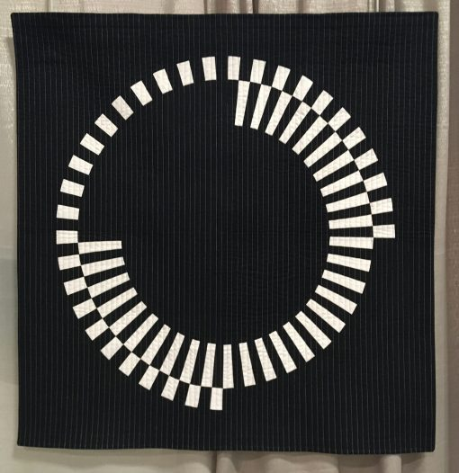 "Modern quilt featured at QuiltCon 2019 — ""Offset"" by Audrey Esarey @cottonandbourbon Statement: ""Offset is an original design. I wanted to explore a design based on one large circle and two high contrast fabrics. I love how the black and white wedges are perfectly offset creating segments that fit together, but do not touch each other. I omitted one wedge of each circle in different areas so the visual weight is balanced. This quilt was designed using EQ8, paper pieced, machine pieced and machine quilted. I used a facing to finish the edges of the quilt."""