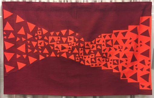 """Modern quilt featured at QuiltCon 2019 — """"Transition"""" by Julie Reuben @b_plus_q Statement: """"As I age, I find myself meditating on change. We begin as one thing and gradually become another. Pieces join together and form a path. To create this quilt, I used freezer paper to piece a number of different triangles in 6"""", 4"""", 3"""" and 2"""" square blocks. I arranged those blocks so the edges of the triangles would create a curving path in which the triangles shift from orange to burgundy. I quilted the path in dense uneven orange lines contrasting with the evenly spaced vertical lines of the background. Bright orange and deep burgundy intermingle but remain distinct."""""""