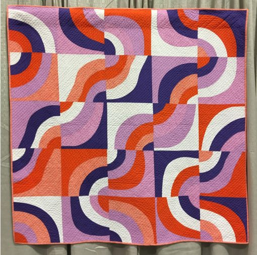 "Modern quilt featured at QuiltCon 2019 — ""Purple Haze"" by Daniela O'Connell @blockMquilts Statement: ""This quilt was made taking part in the Pantone Quilt Challenge 2018 using Ultra Violet as a featured colour. I combined white, a bright orange and a light violet to achieve a vibrant colour combination. For the first time I used curved piecing, all curves are cut without the use of a ruler or a template. Individual blocks are turned in different directions to create an interesting overall design. The simple straight line quilting is to support the diagonal direction the design."""