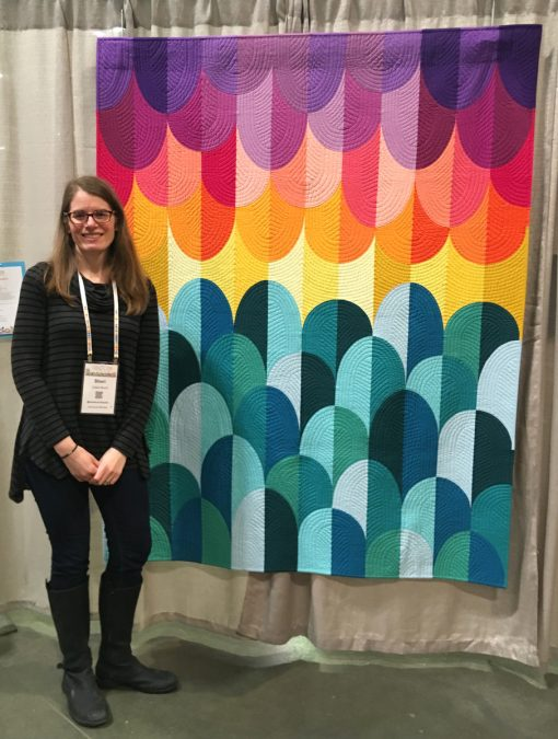 "Modern quilt featured at QuiltCon 2019 — ""Big Island Sunset"" by Sheri Cifaldi-Morrill. Inspiration for Big Island Sunset came from one of my most favorite places in the world—the Big Island of Hawaii. This modern interpretation of the spectacular sunsets on the west coast of Hawaii is entirely pieced from two blocks—a traditional Drunkard's Path and an elongated Drunkard's Path."