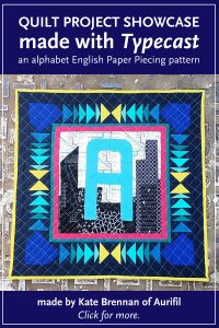 A Alphabet Mini Quilt made by Kate Brennan of Aurifil USA. Chicago skyline made with modern fabric and Typecast English Paper Piecing pattern designed by Whole Circle Studio.