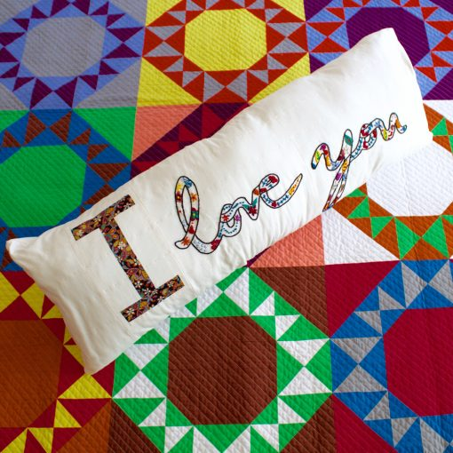 English Paper Pieced letter block (EPP) in a pillow with hand embroidery made by Kim Soper of Leland Ave Studios. Made with Liberty of London Fabric and Typecast EPP pattern.