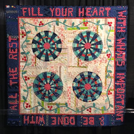 """Wheel of Fortune"" by Pat Sloan. Quilted by Cindy and Dennis Dickinson <br>Statement: ""I wanted to do a Dresden block made up of trips of different widths. I had accumulated boxes of leftover sample strips for creating my round Dresden. Filling the center with a snazzy red polka dot, my Wheel of Fortune came to life."" [Design Source: Aurifil 50wt large cotton thread spools 