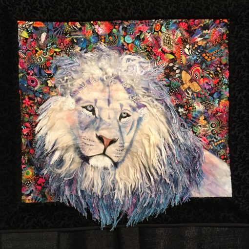 """A Promise Kept"" by Lorraine Turner <br>Statement: ""I met this white lion in a South African sanctuary in 2015. Although he no longer lives in the physical plane, this majestic soul visits me in meditation. His appearances tend to coincide with my wondering if my art is raining awareness of the endangered animals. Aurifil thread as well as alpaca, llama, and lamb's locks are blended into his magnificent mane and his whiskers are horsehair."" [Design Source: Meditation visitations 