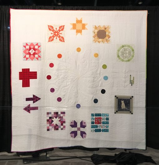 """2017 Designer of the Month Quilt"" by Pat Sloan. Quilted by Carolina Asmussen <br>Statement: ""Designers starting at the top block are:<br>Brenda Ratliff–Bright Sun Block<br>Vanessa Goertzen-Sunflower Power<br>Helen Stubbings-Basically Hugs<br>Heather Givans-Tall Trees<br>Janet Clare-Cat Applique<br>Amanda Murphy-Tight Rope<br>Maureen Cracknell-Dutch Treat<br>Melissa Corry-Scraptastic Stars<br>Sue Marsh-A New Direction<br>Mathew Boudreux-Faux Weave<br>Sarah Maxwell-Star Shine<br>Shruti Dandekar-Reverse Applique Block [Design Source: Quilt Sampler 