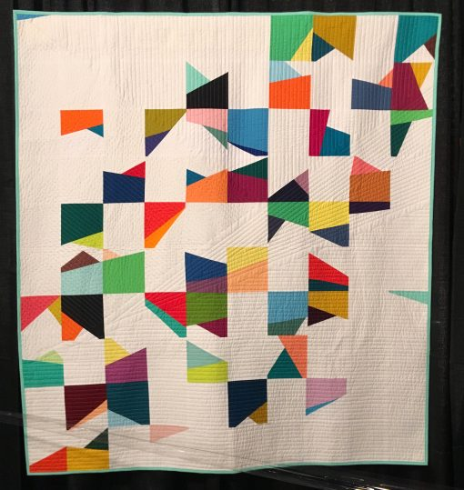 """Correlation"" by Michelle Wilkie Statement: ""A correlation is a statistical exploration of two factors and how they related to each other. In this study, over 100 days, I was investigating the interaction of color and angles. One block was produced each day, and white blocks were used to balance out the intese colored angles. The straight line quilting of the quilt mimics angles from a single block."" [Design Source: Original Design 