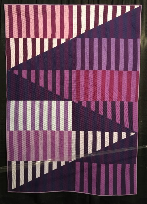 """Ramps"" by Elizabeth K. Ray Statement: ""I designed Ramps for the 2018 Pantone Ultra Violet Quilt Challenge as part of my series on exploring pieced strips cut into half square triangles and gentle curves. Ramps doesn't use curves. I liked the design element with the sharp extending line and used varying hues of purple and violet along with value contrasts to define strong geometric divisions. My goal was to create clear contrasts and crip points bouncing your eye up and down the ramps. The vertical strips are not intended to mach up by act as pieced areas."" [Design Source: Original Design 