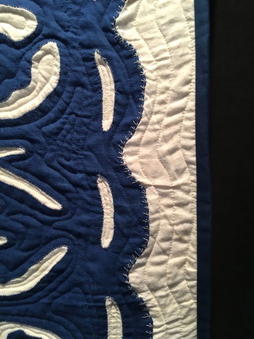 detail of Blue Hawaii by Unknown Maker. Quilted by Ellen Phillips. The quilt top was donated to the Texas Quilt Museum in 2015 by Karen K. Buckley. The top was quilted by local Houston longarm quilter Ellen Happe Phillips in 2018. Echo qulting was selected to complete the quilt in the traditional Hawaiian method. The unknown hand appliquer was an expert in her craft. On loan from the Texas Quilt Museum. Techniques: Hand appliqued, machine quilted. Design Source: Hawaiian quilting. Photo taken at 2019 International Quilt Festival