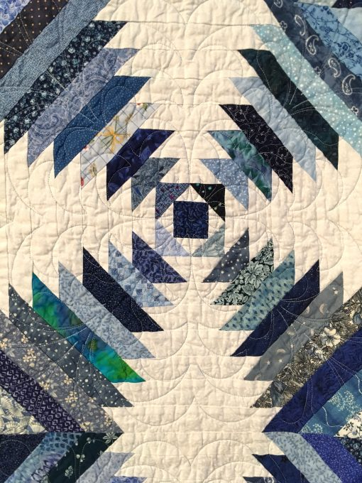 detail of Emily's Pineapple Log Cabin by Sherrilyn O. Phelps. This began as a learning experience for me as a new quilter. It was for my daughter, so she picked the blue and white colors. I learned the block and then added my own borders after I got a longarm quilting machine. It was an exercise in learning. Techniques: Machine pieced. Design Source: Pineapple Log Cabin. Photo taken at 2019 International Quilt Festival