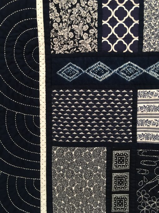 detail of Japanese Memories by Kathleen M. Littfin. I made 16 large blocks, each containing a sashiko piece and one or two shibori pieces, and several other blue and white fabrics in various sizes and styles to complement each other. I'm please that in the finished quilt, it's difficult to discern the blocks. I enjoyed the sashiko so much that I also designed it into the border. There is something so esthetically pleasing about the blue and white quilts, and this quilt contains only those two colors, but many combinations, textures, and patterns.. | Techniques: Hand embroidered, machine pieced and quilted | Design Source: Shibori fabric | Photo taken at 2019 International Quilt Festival