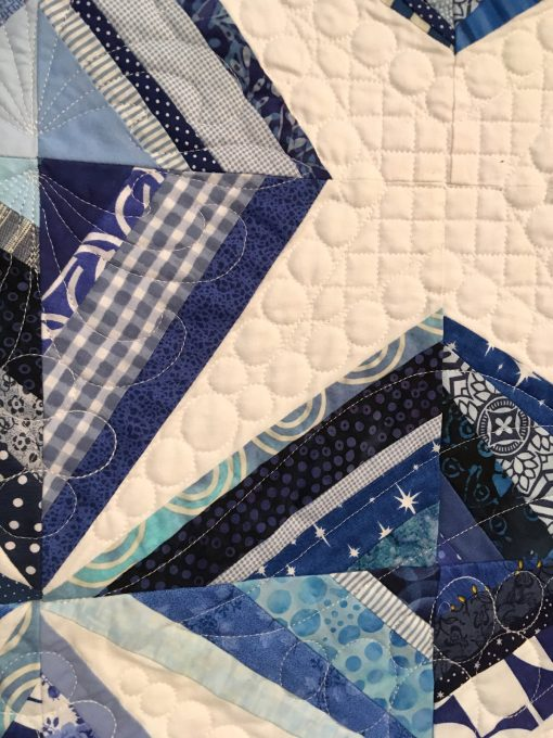 detail of Ice Crystals by Cheryl Degan. Quilted by Emily Bowers. This was my first ever string pieced quilt. I love this quilt because it reminds me of the fun I had sewing with my dear friends on a weekend quilting retreat. | Techniques: Machine pieced and quilted. | Design Source: Images on Pinterest | Photo taken at 2019 International Quilt Festival