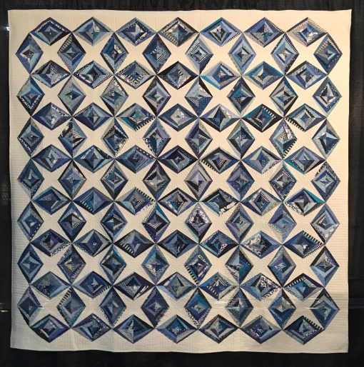 Ice Crystals by Cheryl Degan. Quilted by Emily Bowers. This was my first ever string pieced quilt. I love this quilt because it reminds me of the fun I had sewing with my dear friends on a weekend quilting retreat. | Techniques: Machine pieced and quilted. | Design Source: Images on Pinterest | Photo taken at 2019 International Quilt Festival
