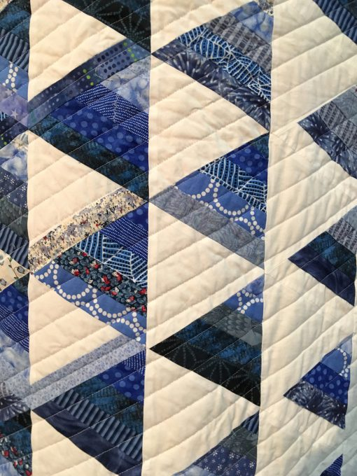 detail of Trifecta by Joy F. Palmer. I saw a similar quilt by Tanya Finken in Fons and Porter's Love of Quilting. I thought I could make a quick simple quilt, but more than three months later, I was still working on it with lots of undoing and mixed up rows. Finally, I quilted it with a longarm machine with the quilt tilted in the machine—also an interesting learning experience. | Techniques: Machine pieced | Design Source: Tanya Finken's quilt in Fons and Porter's Love of Quilting | Photo taken at 2019 International Quilt Festival