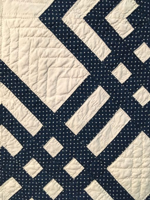 detail of Carpenter's Square by Unknown Maker. An indigo and white Carpenter's Square is distinguished by an unusual diagonal block. Constructed by hand and machine, the quilt features double line hand quilting in a windowpane pattern with a hand stitched binding. On loan from the collection of International Quilt Festival. | Techniques: Hand pieced and quilted, machine pieced | Design Source: Interlocked Squares | Photo taken at 2019 International Quilt Festival