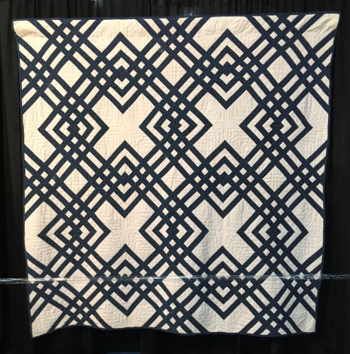 Carpenter's Square by Unknown Maker. An indigo and white Carpenter's Square is distinguished by an unusual diagonal block. Constructed by hand and machine, the quilt features double line hand quilting in a windowpane pattern with a hand stitched binding. On loan from the collection of International Quilt Festival. | Techniques: Hand pieced and quilted, machine pieced | Design Source: Interlocked Squares | Photo taken at 2019 International Quilt Festival