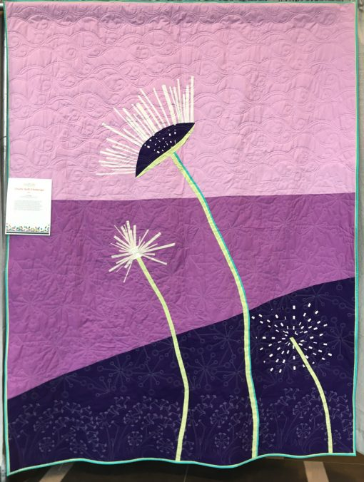 On the Breeze by the Prince Edward Island Modern Quilt Guild (Stratford, Prince Edward Island, Canada) Statement: As a small guild, we collaborated on the concept, as it embodies the principles of a modern quilt and offered a challenge for our members. While working on the design, the dandelions were abundant on the Island. Over a few sew-ins and after careful consideration along the way, members working on this quilt were enjoying improve piecing and trying different techniques to represent the flower getting ready to be on the breeze in search of new grounds. This quilt was truly a collaborative effort. Pieced by Heather, Cathy, Dawn, Jean, Janet, Velda, and Linda. Designed by Heather Jarman and machine quilted by Colleen Henderson. Displayed at QuiltCon 2019 in Nashville, Tennessee.