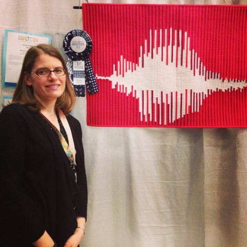 Sheri Cifaldi-Morrill of Whole Circle Studio with her award-winning modern quilt, What's the Frequency, Love?, first place winner in the Small Quilts category at QuiltCon 2015 in Austin, Texas.
