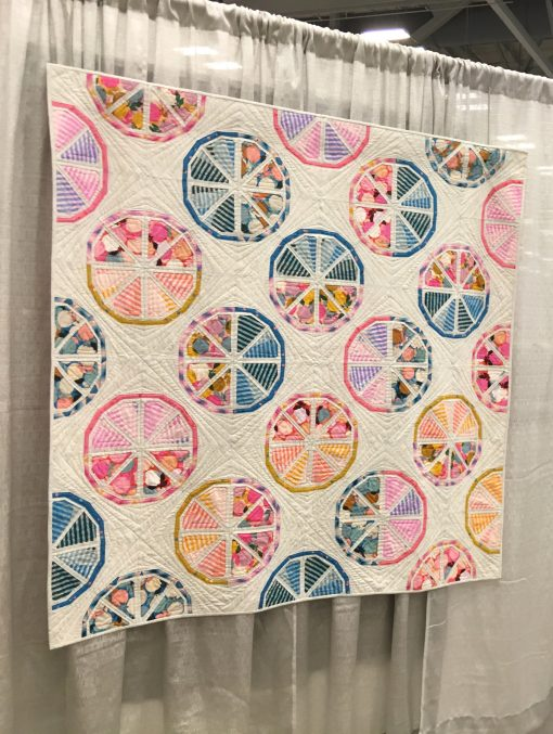 """""""Citrus Slices"""" by Sheri Cifaldi-Morrill @wholecirclestudio Statement: """"Citrus Slices is an exploration in balancing bold prints and graphic pieced shapes with strong graphics created by quilting in the negative space."""" Modern quilt featured in the Piecing category at QuiltCon 2020 in Austin, Texas presented by the Modern Quilt Guild."""