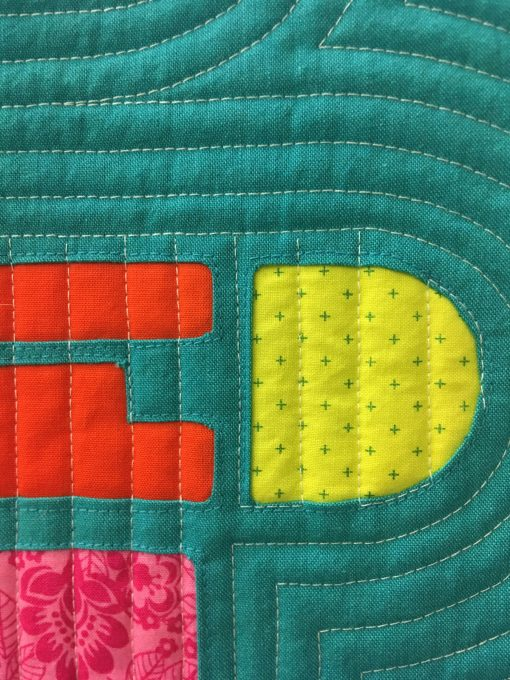 """detail of """"Damned"""" by Skye Rayburn @isleofskyestudio Statement: """"A familiar saying when things just are not going your way. I thought I would use this phrase as I worked through the different angles of the letters/shapes using the reverse applique technique."""" Modern quilt featured in the Small Quilts category at QuiltCon 2020 in Austin, Texas presented by the Modern Quilt Guild."""
