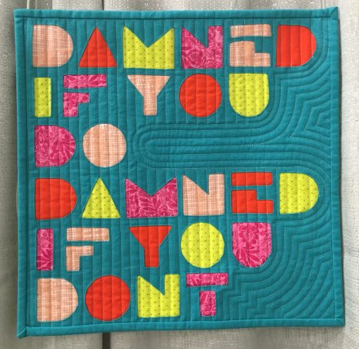 """Damned"" by Skye Rayburn @isleofskyestudio Statement: ""A familiar saying when things just are not going your way. I thought I would use this phrase as I worked through the different angles of the letters/shapes using the reverse applique technique."" Modern quilt featured in the Small Quilts category at QuiltCon 2020 in Austin, Texas presented by the Modern Quilt Guild."